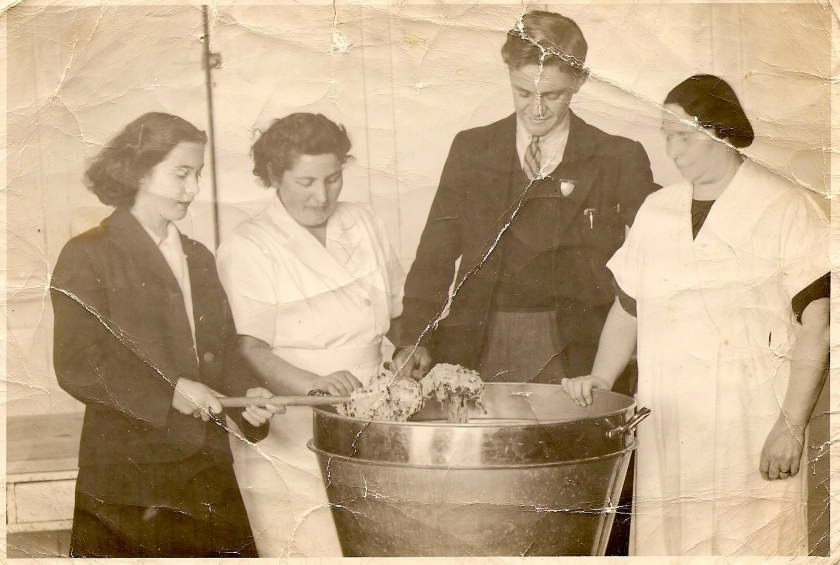 A man and three women with a large bowl of cake mix