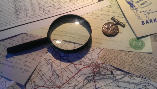 Photograph of maps, documents and a magnifying glass