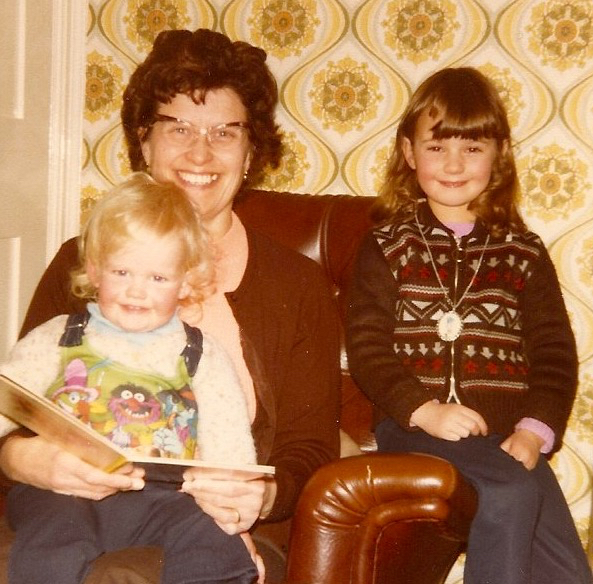 My grandmother, reading me a story, whilst my sister pretends to be angelic.
